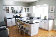 white kitchen with steel gray granite countertops. Ikea lamp shade pendant over sink with gold leaf inside.