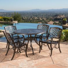 A contemporary take on a timeless patio staple, this round dining table brings enduring style to your outdoor ensemble. Made from cast aluminum in a hammered bronze finish, this weather-resistant design features a lattice and scrollwork tabletop a convenient umbrella hole, and gently curved legs. To create a classic seating group on the back patio, start by rolling out a tonal-striped outdoor area rug to define the space, then arrange four wrought-iron chairs around this charming table…