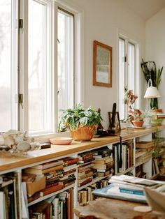 love the long, low book shelving under the windows and all the natural elements