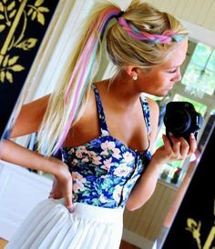 Long blonde hair tied up in a ponytail with a gorgeous pastel rainbow colored braid!