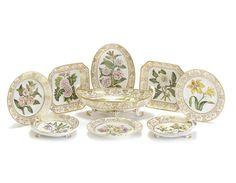 A Coalport botanical dessert service, circa 1805 Fully painted in bright enamels with titled specimens of fruit and flowers, within gilded neoclassical borders, comprising a boat-shaped centrepiece painted with an 'Orange Tree', four oval dishes, four shell dishes, two square dishes, nine plates and a stand from a sauce turee