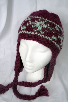Patterned beanie with braided ties.