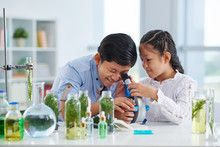 Curious Asian boy and girl using microscope in class