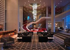 The W Hollywood has patterned carpeting, elegant lounge furniture, perforated accent wall, a sweeping stair with red carpeting, and large hanging chandelier.