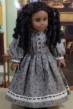 This beautiful grey dress is the perfect thing for your historical doll to wear during the cold of winter. The dress is made from a floral-on-grey high quality cotton fabric. It features pleats across the bodice, decorative buttons down the front, and lace around the neckband, sleeve cuffs, and near the hem of full skirt. The dress fastens in back with snaps. The doll, socks, boots, and scenery were used for modeling purposes only and are not included with this listing.  Machine washable…