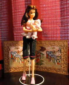 Momoko Doll with baby. The Momoko doll, like most Asian fashion dolls, has visible joints and good flexibility, able to tilt and rotate her head, bend and rotate the elbows, bend the knees, slightly flex and bend near the waist, flex the wrists and ankles, and so on. The Momoko doll is able to stand on her own without help, though a white metal stand is included.