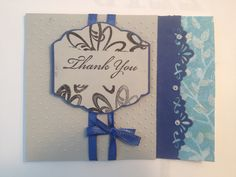 The cut-off effect of the flowers around the sentiment was created by temporarily adhering a bit of scrap paper over the area I wanted to leave blank, in the case rectangular. I then stamped the words in the empty spot. A simple cuttlebug embossing on the grey background nicely offsets the unembossed sentiment. The blue and white patterned edge is touched up with a bit of white ink topped off with clear, glittery embossing powder.