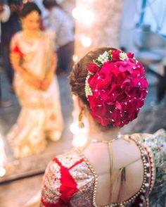 Indian Bridal Hairstyles - WedMeGood | A Big hair bun with floral hairpins, and rose petals! #bridal #hairstyles #wedmegood