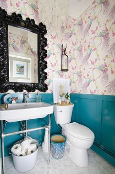 A small powder room gets a majorly gorgeous makeover, including marble tile, teal wainscoting, console sink, bird wallpaper, and capiz shell pendant. You won't believe this before and after!