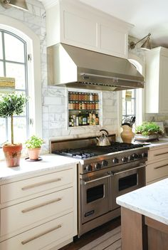 range and hood, built in spice shelving, windows, marble to the ceiling, swing arm sconces over windows.