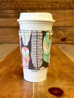 Fabric Coffee Cozy -- PASTEL FEATHERS -- Fabric Coffee Sleeve, Java Jacket, Coffee Sleeve, Coffee Cup Holder by LotusBlumeBoutique on Etsy https://www.etsy.com/listing/492225146/fabric-coffee-cozy-pastel-feathers