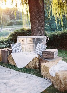 Photo booth inspiration: hay bales, lace tablecloth backdrop, BHLDN fans hanging.