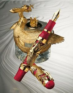 Rare artist's proof Montegrappa Eternal Bird 18K Solid Yellow Gold & Fountain Pen & Inkwell, created in 2005. The pen features a heavy, elaborately hand-finished 18K solid yellow gold phoenix overlay, set with 244 brilliant-cut diamonds (about 3.2 carats), and with rubies set in the phoenix's eyes. The pen is accompanied by an 18K solid yellow gold and Madagascar crystal rock inkwell. Sold at auction for $44,000