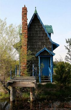 Curious angles, rippling trim, and a turquoise roof--is the house in this photo real or something from a fairytale?