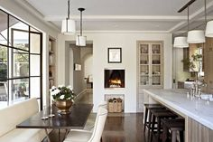 Fireplace in kitchen love the black framed windows and white painted room