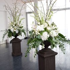 Lush urns with flowering cherry blossoms and white florals flanking wedding ceremony:
