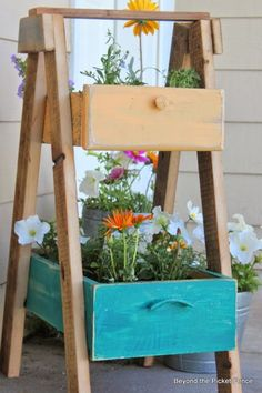 This tiered planter was built using drawers to house colorful blooms. Learn more at Beyond The Picket Fence.