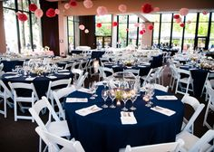 "DIY coral pompoms hung from the ceiling. Rentals from Raphaels in San Diego. Navy table cloths, white chairs, white napkins, 6"" tables had rectangular wooden boxes, and round tables had glass bowls."