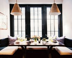 A built-in banquette and pair of light fixtures in a breakfast nook designed by Christina Murphy & Meg Gabriele.