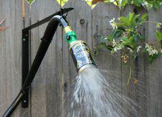 Create your own outdoor shower using an old aluminum can, hose, and brackets
