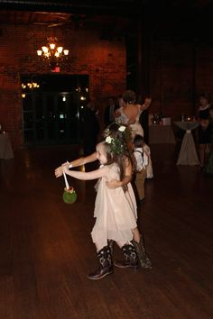 Flower girl dancing with pomander ball and floral crown