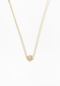 This necklace features a layered look with double chains and an oval-shaped pendant with a delicate fossil design.