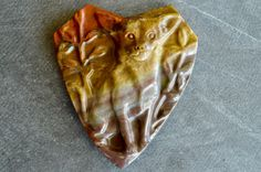 Hand carved stone dog pendant depicts a sweet Chihuahua.  The stone color is shades of red, brown, and yellow.  The stone is natural Succor Creek Jasper, with no color enhancements.   I can't say enough how gorgeous this piece is, and what  superb craftsmanship is used to make this one of a kind stone pendant.  Pendant is drilled from front to back.  Designer quality pendant.     Measurement is 60x50x9mm.   Weight is 140 carats.      This adorable, carved dog pendant is handcrafted out of…