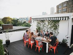 rooftop dining - love the pop of color in the chairs, and that awning!