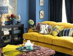 deco bleu et jaune dans in salon vintage, canapé jaune pastel, mur couleur bleue, table basse vintage, peinture murale retro, tapis motifs floraux retro