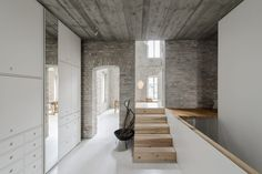 This heritage building conversion in Berlin accommodates a family and their three children.Exposed brick walls add personality to the interiors.