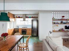 Living | A parede com cobogó, da Elemento V, isola a lavanderia e tem pranchas de madeira que compõem o home office. Cadeira da Herrero Antiquário. Luminárias da Lumini (amarela) e da Loja Teo (cromada). Na cozinha, armários da Bomlar Marcenaria (Foto: Fran Parente)