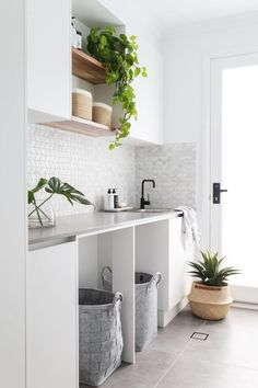 A modern white laundry with sleek concrete Caesarstone bench tops, concrete look. A modern white laundry with sleek concrete Caesarstone bench tops, concrete look tiles and black fi Laundry Doors, Laundry In Bathroom, Modern Laundry Rooms, Laundry Shelves, Timber Shelves, White Shelves, Laundry Room Inspiration, Interior Inspiration, Design Inspiration