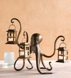 Our unusual Octopus Lantern has no trouble lending a tentacle or three to add some soft light to a room. Three of its eight tentacles hold a small lantern, while its other five gracefully curve underneath to provide a base of support. A beautiful and unexpected piece of art, this octopus lantern is crafted of aluminum and iron with glass insets in its three lanterns. Bronze finish.