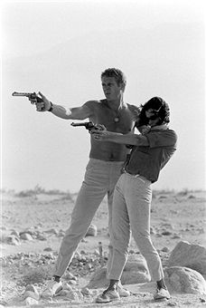 AIMING HIGH - Steve McQueen & his wife Neile aim at targets with their handguns.   .