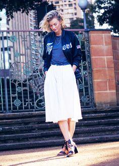 Zanita wearing a bomber jacket, white midi skirt, and block heels