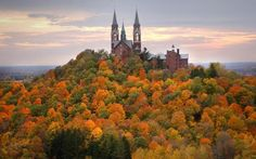 Holy Hill rises above a mass of trees in fall colors near dusk. For fall leaf watchers with the stamina to climb the stairs, the views are great.