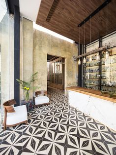Decorative black and white patterned tiles flow throughout this modern restaurant and add a sense of continuity to the space.