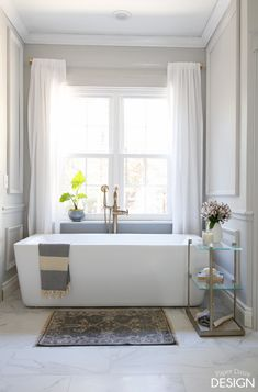 Stunning soaker tub under a window in marble master bathroom remodel. See site for more. Upstairs Bathrooms, Master Bathroom, Bath Under Window, Black And White Backsplash, Small Round Rugs, Sloped Yard, Soaker Tub, Bathroom Windows, Southern Homes
