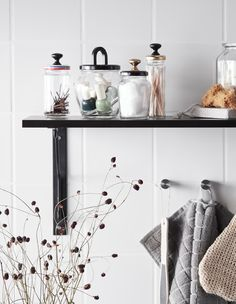Glass food jars given a new life as bathroom storage with kitchen knobs glued onto lids
