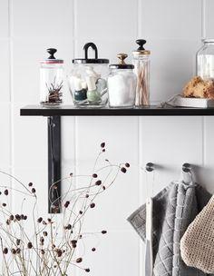 Szklane słoiki odżywają jako pojemniki do przechowywania w łazience z kuchennymi gałkami przyklejonymi do pokrywek.
