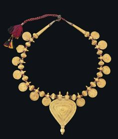 A GOLD NECKLACE  TAMIL NADU, SOUTH INDIA, 19TH CENTURY  Probably a wedding necklace, with large triangular pendant ending with spherical ribbed finial, the dense decoration with central embossed and applied rosette, bordered by concentric bands of gold filigree arranged between granulated lines, the lace with seven gold repoussé discs to either side, each with floral spray, arranged between ribbed spherical elements, with tapering finials, strung on metal-thread embroidered red thread