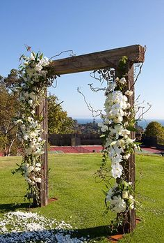 Wood wedding ceremony arch with white orchid and rose decor