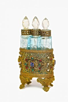 c1920 Czechoslovakian perfume bottle trio, cased pale blue crystal cut to clear, facet dauber stoppers, jeweled filigree metal holder. 3 7/8 in.