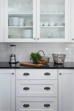 Farmhouse kitchen cabinet ideas. Simple farmhouse kitchen with white cabinet, black granite countertop, white subway tile backsplash and glass door upper cabinets. #Farmhousekitchen Tim Cuppett Architects.