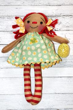 Happy Easter! This sweet holiday doll is 8 inches tall and wearing a really cute egg print dress trimmed in lace with a vintage button. She has a loop on the back of her head so she could be used as an ornament or a shelf sitter. Attached to her hand is a yellow Easter egg. This sweet doll would make a lovely Easter or spring gift to yourself or a friend!  This doll is one of a kind and uniquely made. The doll you see in the photo is the doll you will receive. Her face and heart are hand…