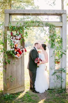 Boho chic wedding ceremony decor idea - outdoor wedding arch made of a repurposed doorway with greenery + flowers {Brandy Angel Photography}
