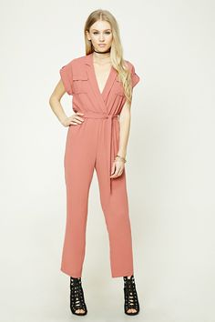 A woven jumpsuit featuring a belted waist, surplice neckline, notched collar, epaulets, short cuffed sleeves, two front flap chest pockets with a pleated center, an elasticized waist, and button keyhole back.