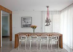 Sala de jantar | Mesa de madeira de demolição com cadeiras da Kartell. Pendente da Micasa. Vaso da Benedixt. Sofá da Decameron com almofadas da Conceito Firma Casa. Foto da Galeria Lume