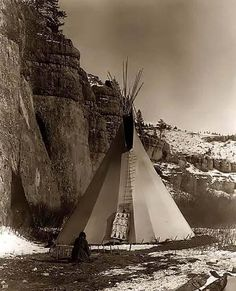 Indian Woman Stretching Hides in front of her Tipi. It was made in Montana in 1908 by Edward S. Curtis.The photo illustrates a Crow (Apsaroke) woman stretching a hide that has been secured to the ground by stakes. There is a wonderful view of her tipi in background, and a cliff on her left.