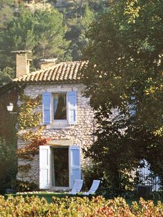 French farmhouse with pale blue shutters.